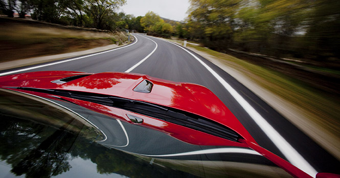 View looking down the hood of a red sports cars speeding down a road
