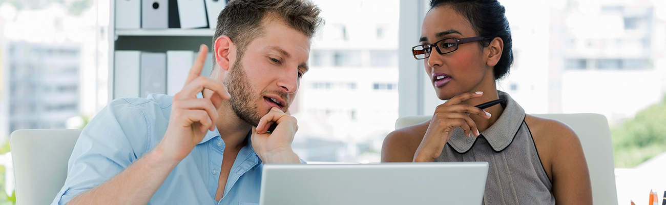 man and woman discussing business plan while viewing laptop