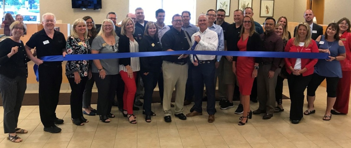 Large group of Blackhawk Bank employees holding a blue ribbon with Dave Adkins, Blackhawk Bank president, holding large scissors preparing to cut the ribbon for the dedication of the McHenry Banking Center inside the lobby.