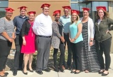 Group of Blackhawk Bank Leadership Academy graduates wearing red graduation caps standing in front of the Roscoe Banking Center