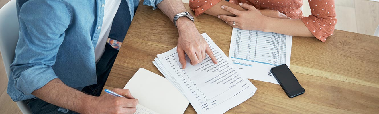 Man and woman looking over financial statement.  Woman has her arms crossed while the man holds a pen and points at the financial statement.