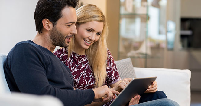Man and woman smiling while doing online banking on a tablet.