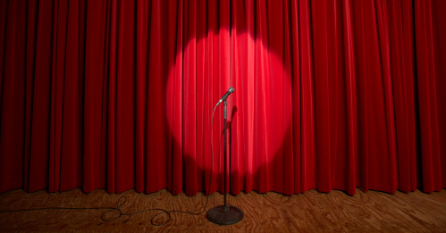 A lone microphone on stage in front of a red curtain.