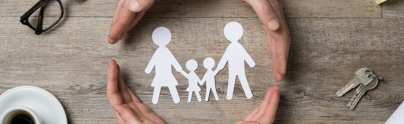 Two pairs of hands encircling paper cutout of family of four on wooden table describing future family
