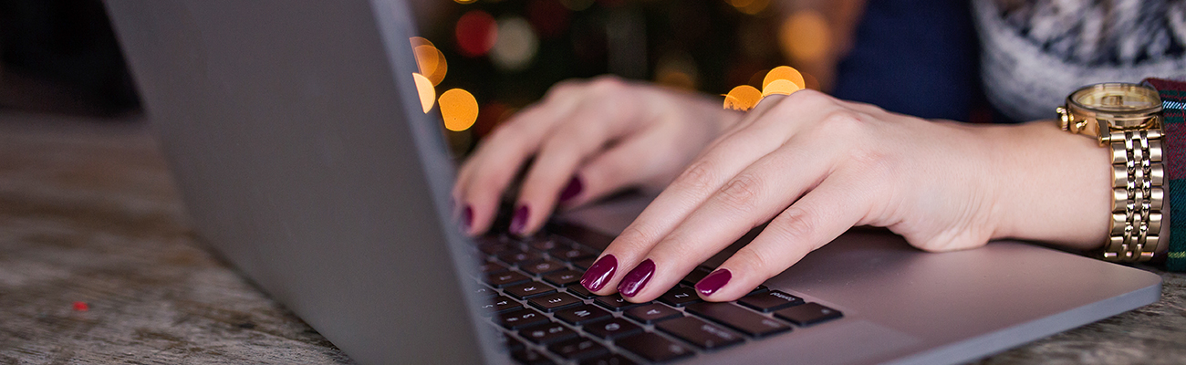 Woman's hands typing on a lap top.