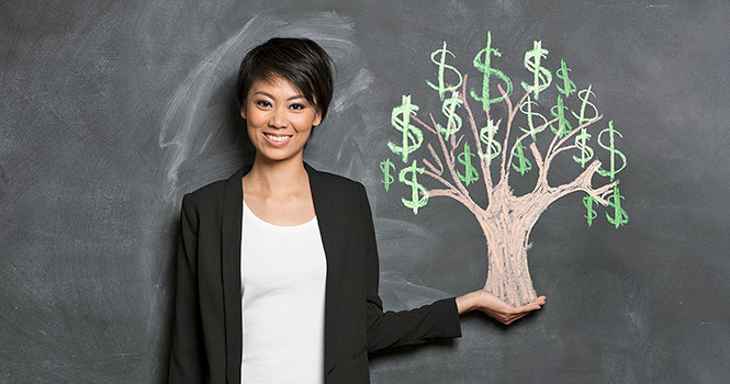 A woman with short dark hair is placed against a chalkboard background with her left hand extended.  It appears that the left hand is holding an image of a tree with dollar signs as leaves, which is drawn on the chalkboard.