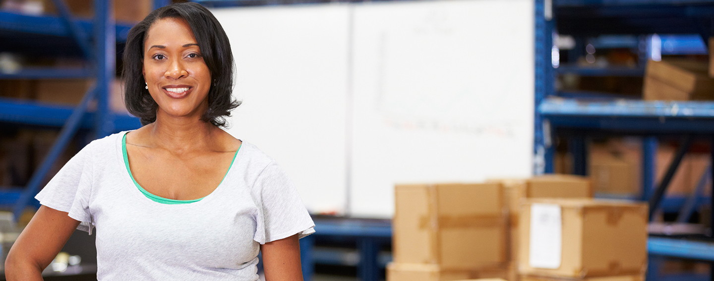 Woman standing in a warehouse with boxes behind her.