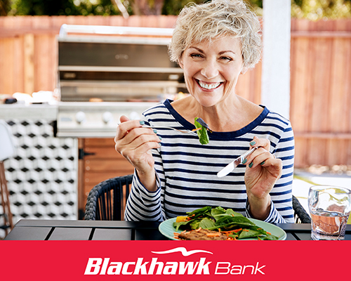 Senior Women wearing a black and white striped shirt smiling while sitting at a table eating salad