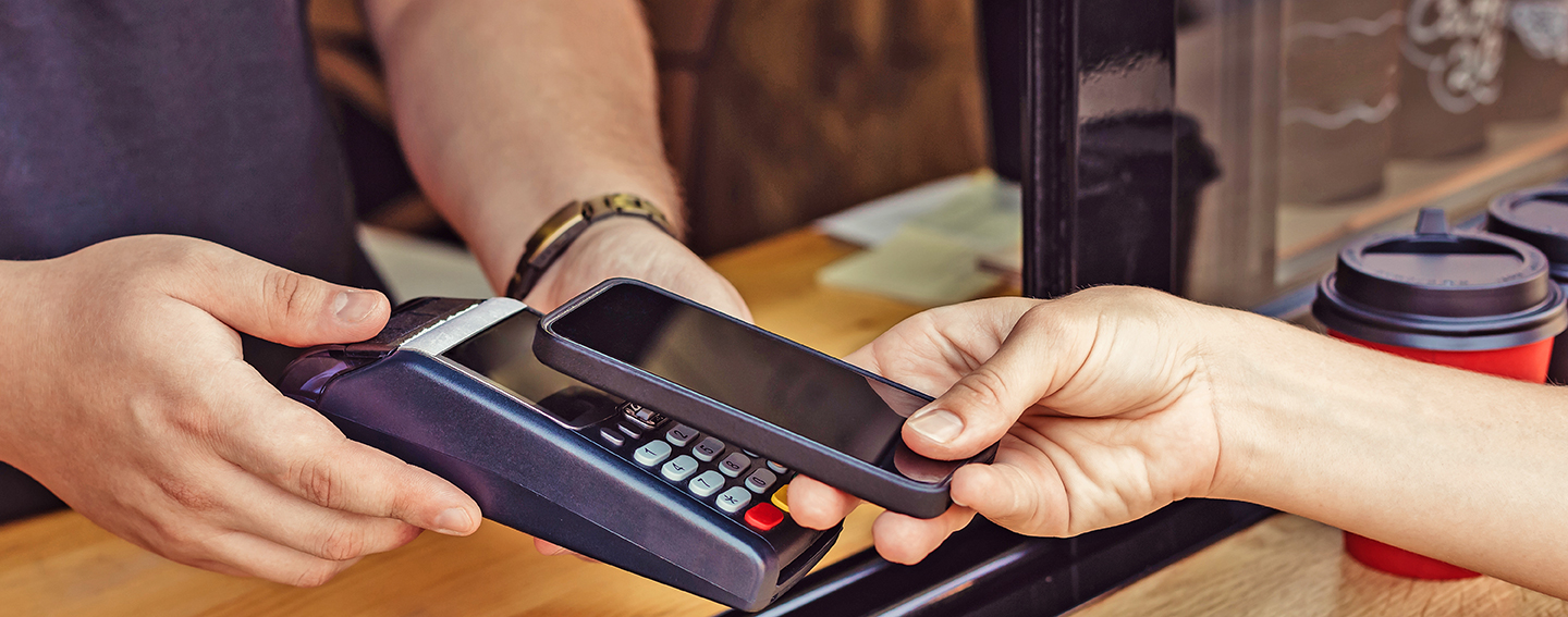 Customer holding phone over merchant credit card machine to pay digitally with Digital Wallet