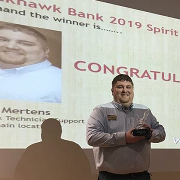 Brian Mertens holds trophy for winning the 2019 Blackhawk Bank Spirit Award